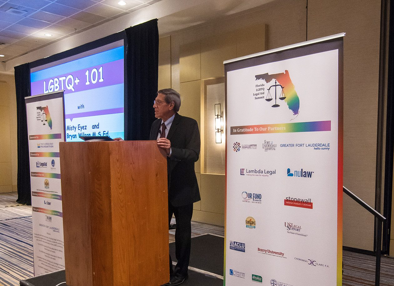 Tony Karrat at a podium opening the LGBTQ Summit.
